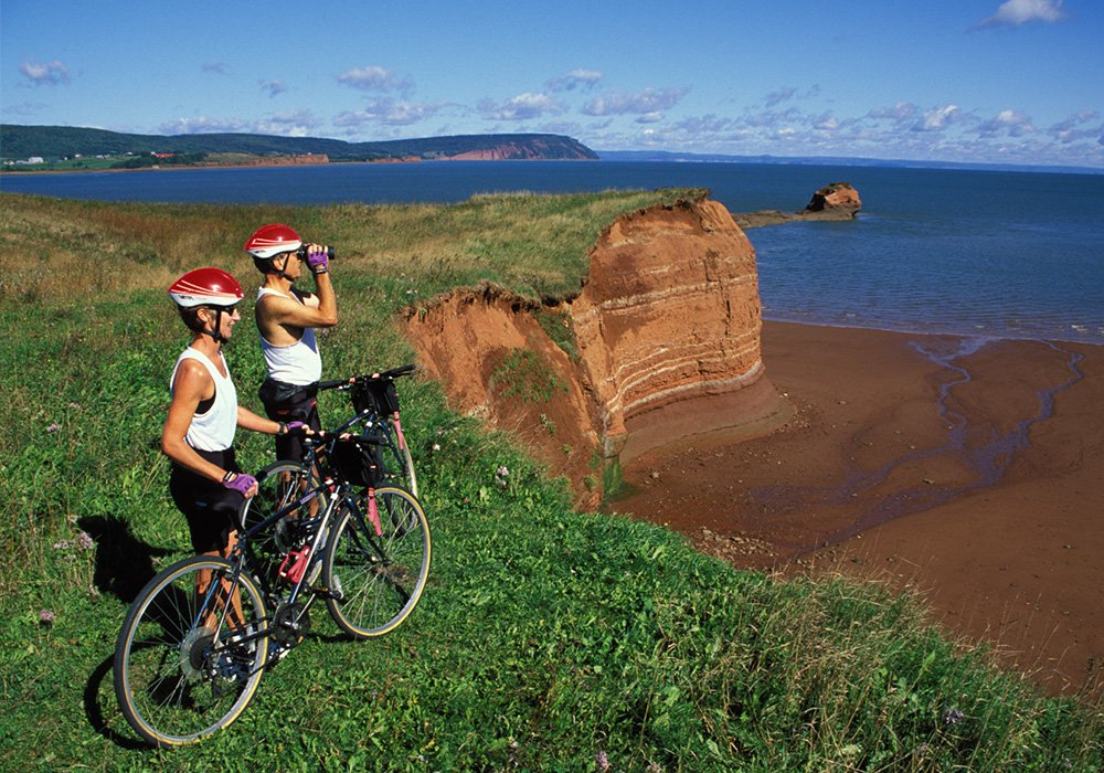 An image rendering of two bikers with binoculars in Annapolis Valley by the water.