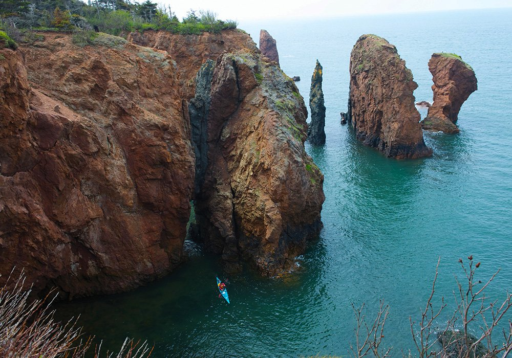 An image rendering of a person kayaking in the ocean by big rocks at the Bay of Fundy.