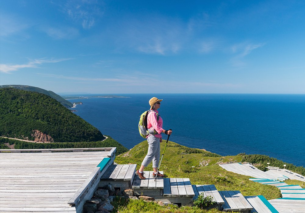 An image rendering of a woman starting the Cabot Trail on a sunny day.