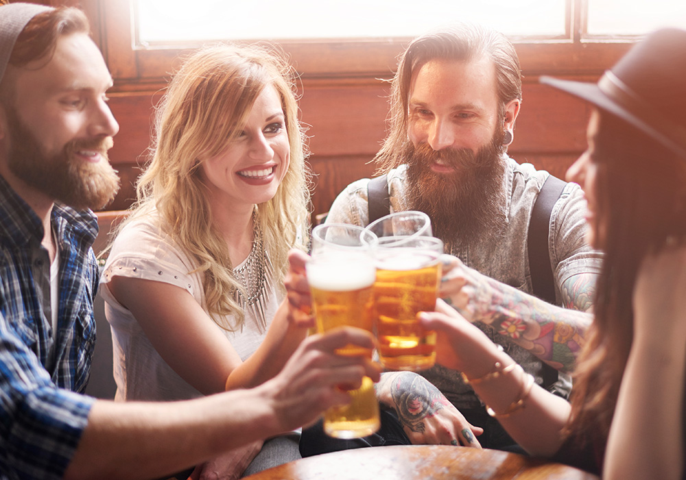 An image rendering of four people having a beer in a pub.