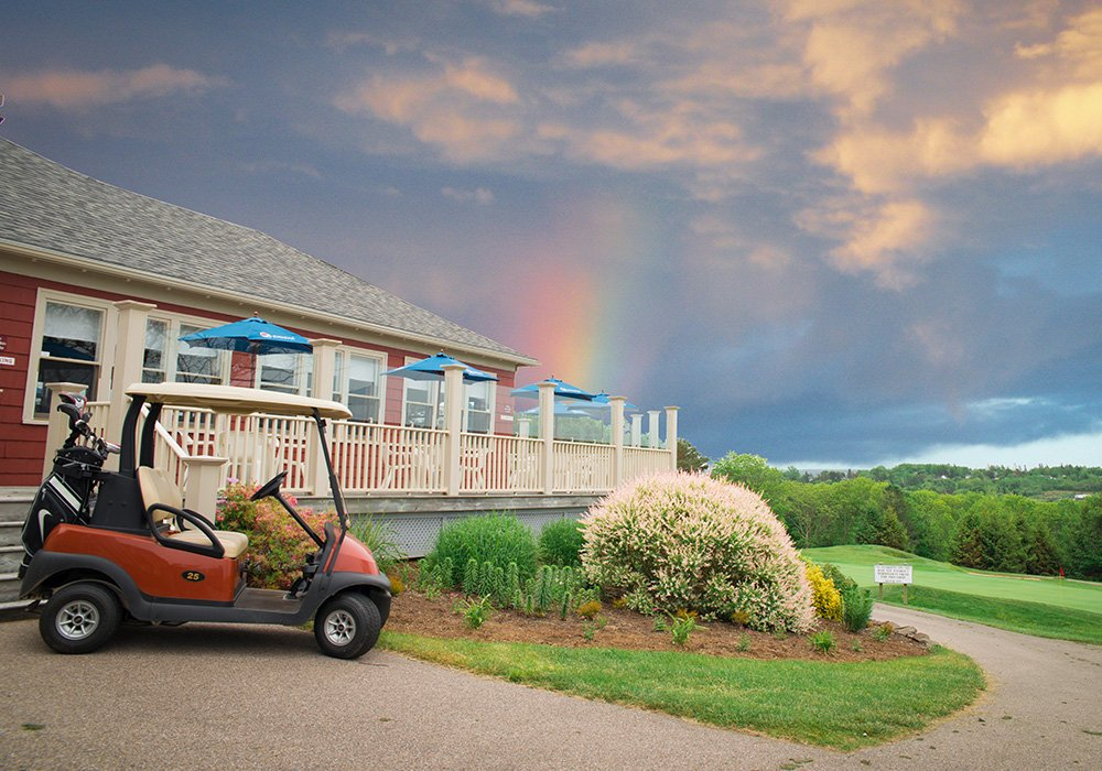 An image rendering of restaurant and golf cart surrounded by trees with a rainbow in the sky.