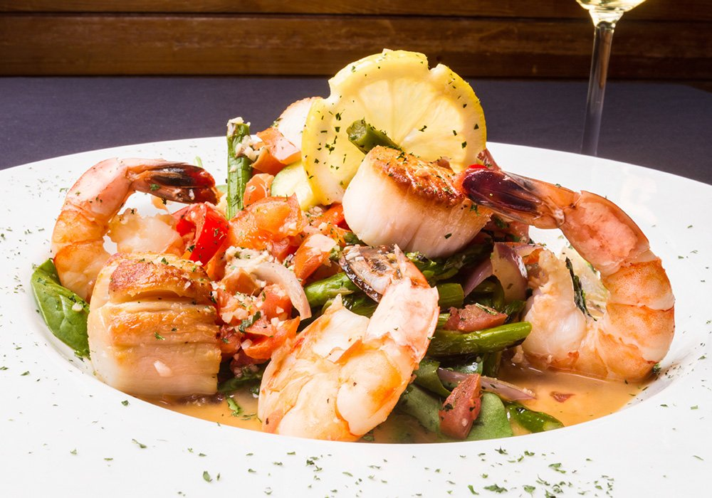 An image rendering of dish of food with scallops,shrimp, lemon, and asparagus.