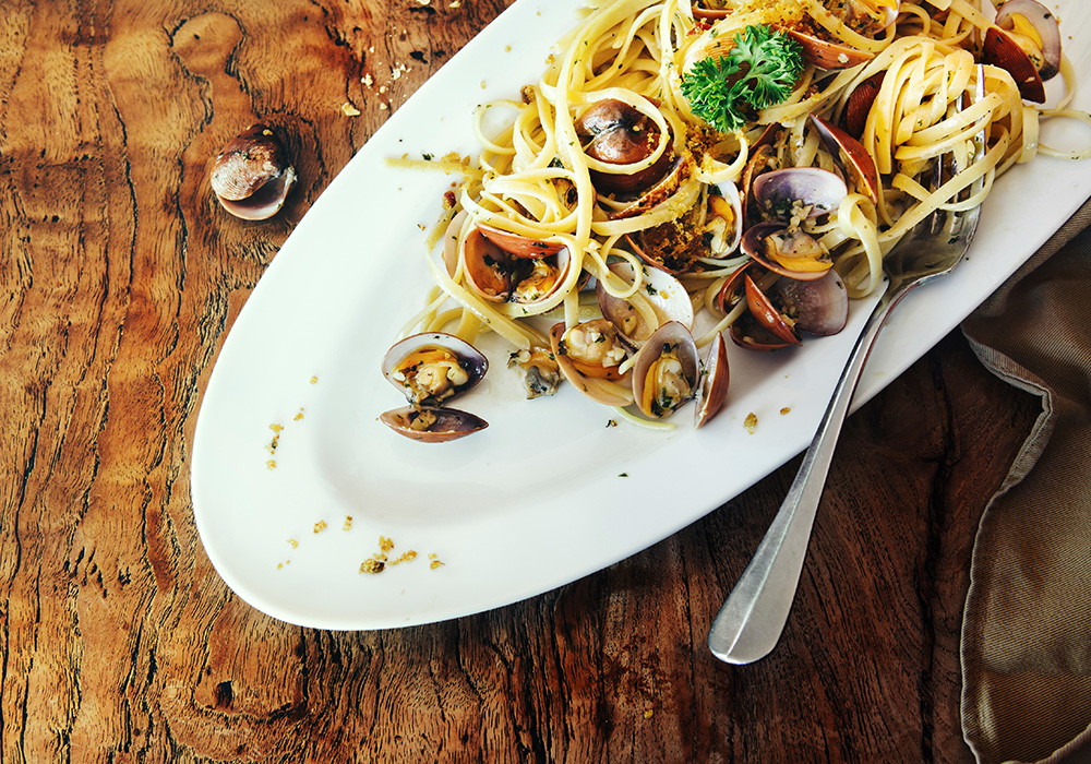 An image rendering of a plate on a wooden table with pasta, mussels and a fork in it.