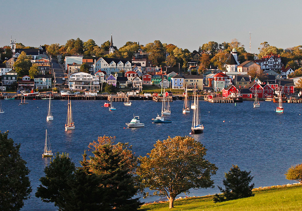 An image rendering of sail boats and colourful houses in Lunenburg, on a sunny day.
