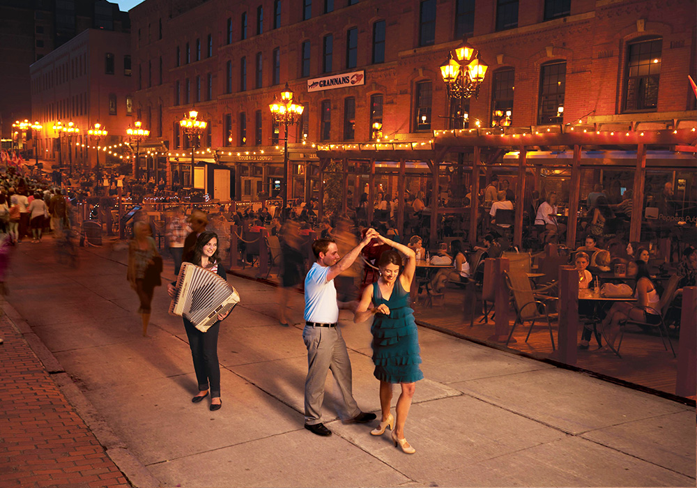 An image rendering of people dancing in a courtyard at night beside restaurant patios.