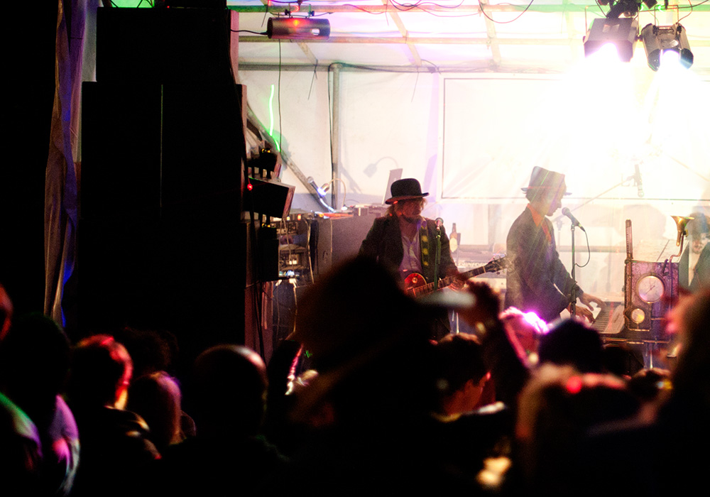 An image rendering of people in a crowd dancing at a concert with two men on stage at night.