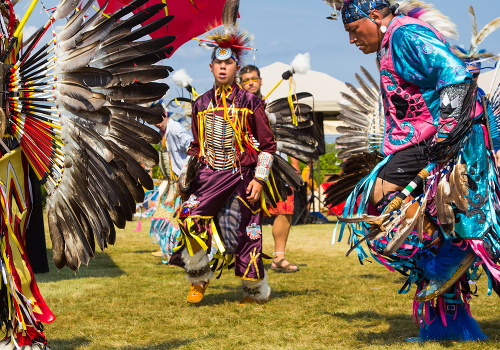 An image rendering of a festival with people wearing colourful costumes and feather headdresses.